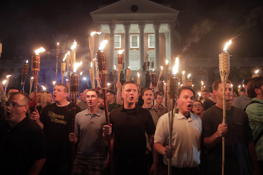 "These are the monsters we mock. Young white men (probably a few older ones, mixed in, but that's the only mixing), unaware of inadvertent comedy, clueless about the cartoon quality of tiki torches. They say the same vile shit their ancestors did, but they must know they're extras in someone else's film. Someone with more power, more authority, more vision. There's no vision here, not a speck. Aargh.  The ones who aren't marching are also zombies. They'd never march, in fact, and in some cases they're offended by this open hatred and puffed-up bigotry, although God knows they voted for it. Whether they have some rudimentary, lizard-brain notions of political philosophy and have picked one they like, or they're just—as I suspect—passive receivers of whatever someone shoves onto their screens, they're still the walking dead of our once impressive republic.  The truth is out there, and it's not hidden at Roswell. It's where it always has been, in a well-disclosed location known as In Plain Sight, but these undead…boy, I don't know. Their information-gathering skills seem limited by their cable subscriptions and car radios, and how easy was that, Mr. Murdoch? Give them biases that are totally confirmatory of their worst fears, then tell them THIS IS THE ONLY TRUTH. DON'T BELIEVE ANYONE ELSE.  And they don't. Of course. So maybe they're lost, doomed to shuffle the landscape in search of brains, a natural instinct, if apparently hopeless. Nature abhors a vacuum, and I assume their crania are already being filled with non-white matter, the way my basement has all those books. Apologies to books.  These shuffling paleo-people, the ones in the photo, who might as well be wearing T-shirts that proclaim their inability to get a prom date? Nothing but fodder, drones in a battle that they can't possibly grasp with their tiny hands. Annoying, alarming, and capable of great mischief, they're unaware of their irrelevance for anything but distraction while power plays alone.  So we get distracted, and the showrunners get more rich and more powerful. We sometimes, even, willingly toss coins their way, buy their wares, watch their ""news"" and their reality television, unaware that we're forging our own nails for our own coffins. Oh, it's only  The Bachelorette , we say. Harmless. It's only a horoscope, or essential oils, or whatever fantasy we decided to invest in, because life is hard and awfully boring, anyway.  They've always wanted to run the show. Their philosophy will always be in the minority, by definition, but their power is growing and now overwhelming. They see themselves as Randian road warriors, a tiny sliver of humanity that can actually do things, and in some ways they're right. They know how to accumulate wealth and power, and their prophecies seem awfully self fulfilling now. They are now in ascendancy, they are quite often brilliant, and they have no souls, not really.  It's never been about the zombies. These wannabe Klansmen are just foot soldiers. It was always going to be about the vampires."