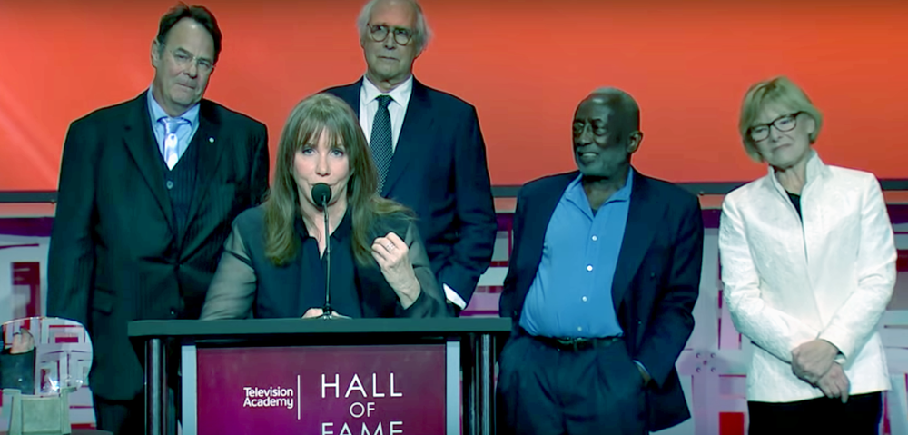 Back row: Dan Ackroyd, Chevy Chase, Garrett Morris, Jane Curtin. At podium: Larraine Newman.