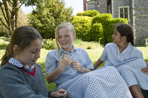 Girls relaxing on the lawns at Sompting Abbotts Prep School