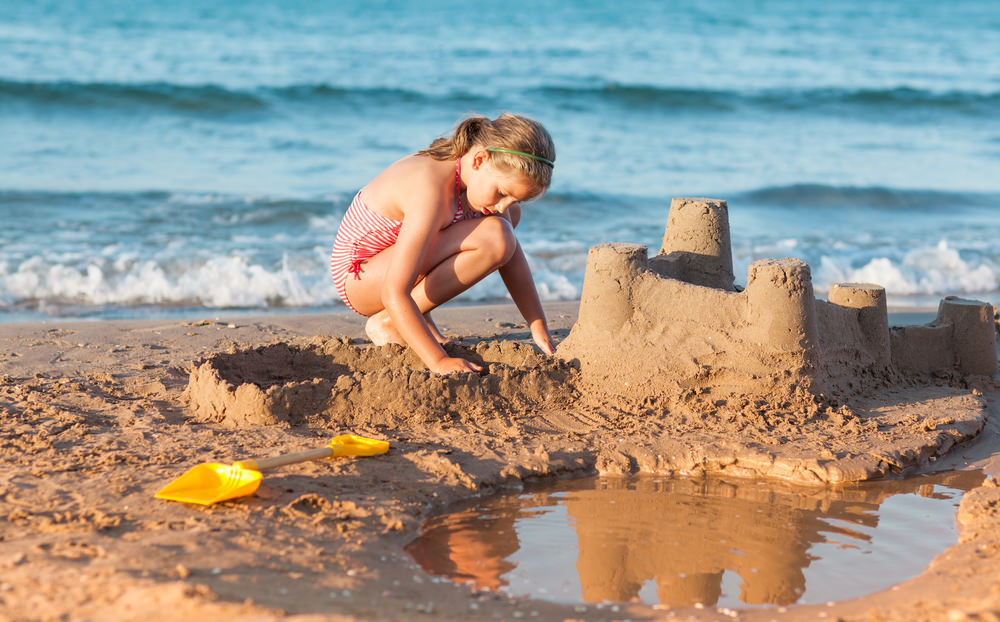 child on beach with sandcastle.jpg