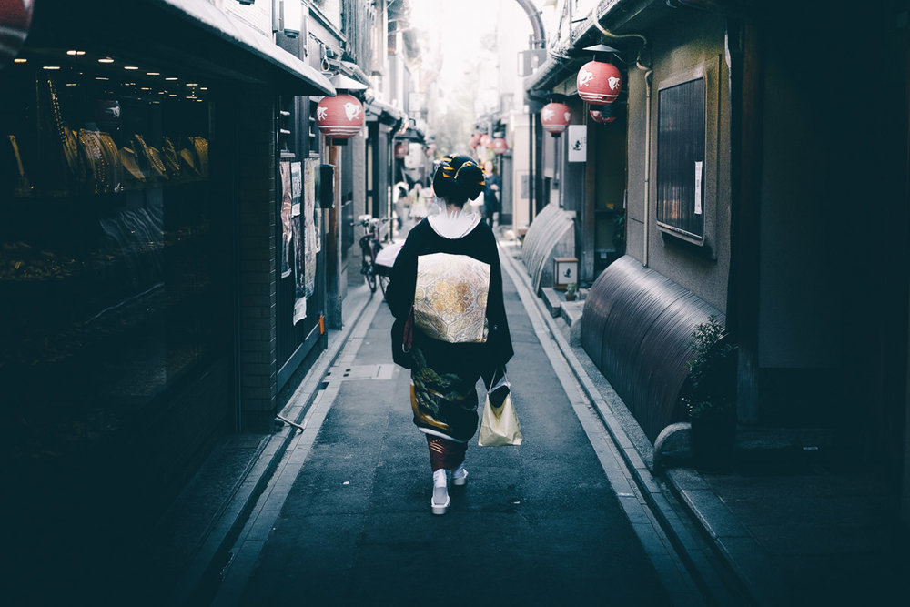 A maiko walking down a traditional Kyoto alleyway. Maikos and geishas are undoubtedly popular amongst street photographers and tourists alike here in Kyoto. I try to avoid taking too many photos of these traditional Japanese entertainers but sometimes a shot lines up for you so well that you can't help but snap a few cheeky photos.
