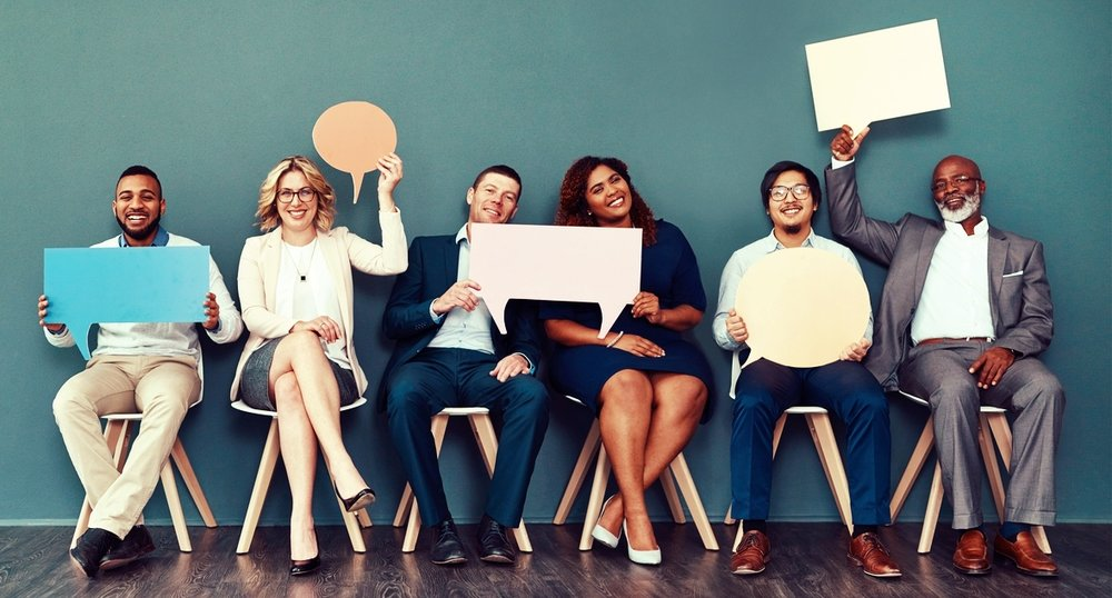 Staged photo of 6 adults sitting along a wall and holding up speech bubble signs