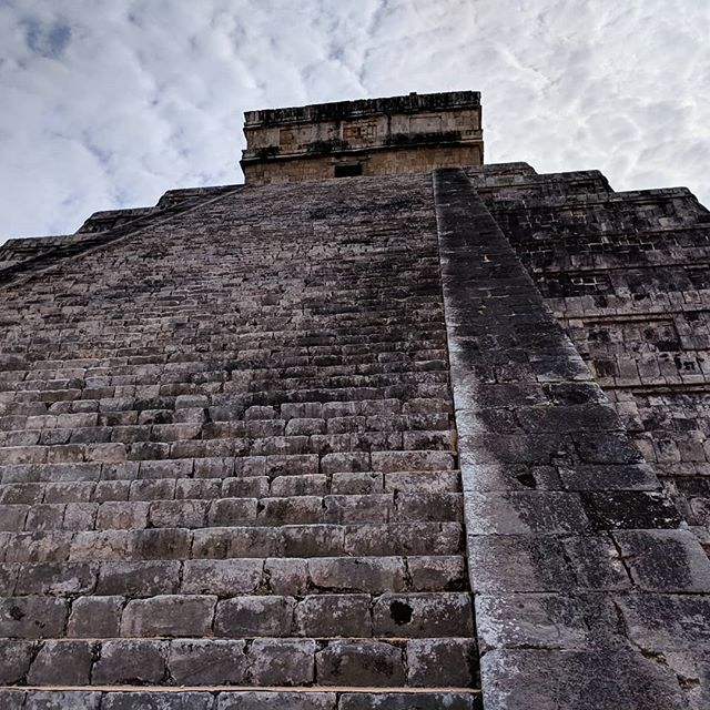 "According to the Moon guide book, ""El Castillo was built according to strict astronomical guidelines. There are nine levels, which, divided by the central staircase, make for 18 platforms, the number of months in the Maya calendar.  Each of the four sides has 91 steps, which, added together along the platform on top, total 365--one for each day of the year. And there are 52 inset panels on each face of the structure, equal to the number of years in each cycle of the Mayan Calendar Round. ""On the Spring and Autumn equinoxes, the afternoon sun lights up a bright zigzag strip on the outside wall of the north staircase as well as the giant serpent heads at the base, giving the appearance of a serpent slithering down the steps""--Moon, Yucatan Peninsula by Liza Prado and Gary Chandler  #chichenitza #onitsown #moonguide #lizaprado #garychandler"