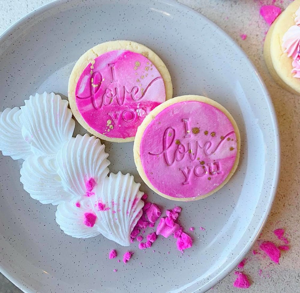 """"""" I Love You"""" Sugar Cookies - Pack of 4 = $15.00Custom message +$9.00Add a pack of 4 to your cake order $12.00Meringue Hearts(4 per bag) = $6.00Add to your cake order for $4.00"""