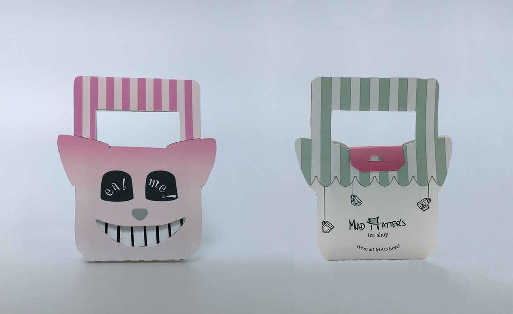 "scone packaging featuring a die cut smile cheshire cat in the front and a branded mad hatter's ""mad hatter"" with top hat in back"