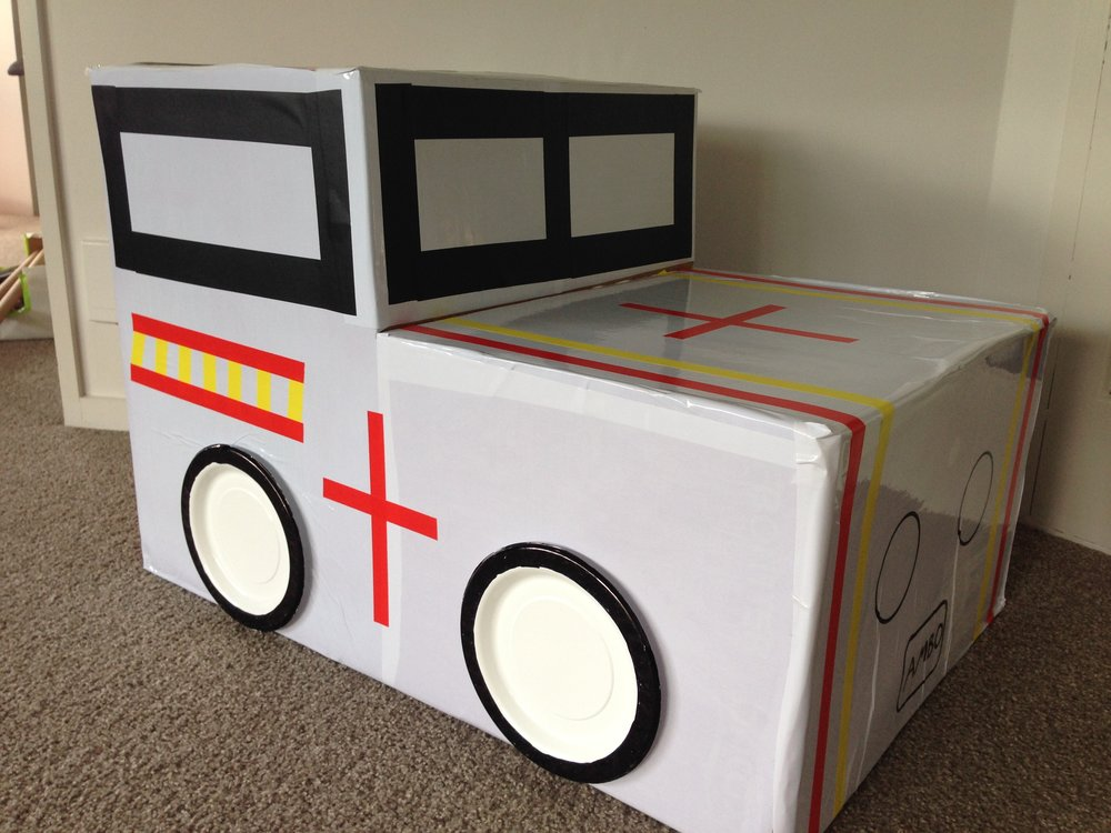 Cardboard car - Instructions1. Cover a large cardboard box in duraseal or wrapping paper 2. Decorate with plastic plates for wheels3. Use different colored tape for windows/doors**We made an ambulance but you could make a fire engine, police car etc