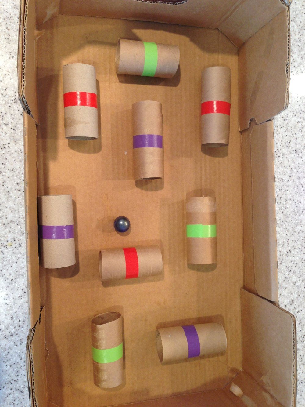 Marble maze - Instructions1. Tape different color tape around toilet rolls (for different points)2. Glue or tape the toilet rolls in a cardboard box3. Move the box around to get the marble through the different tunnels to get points