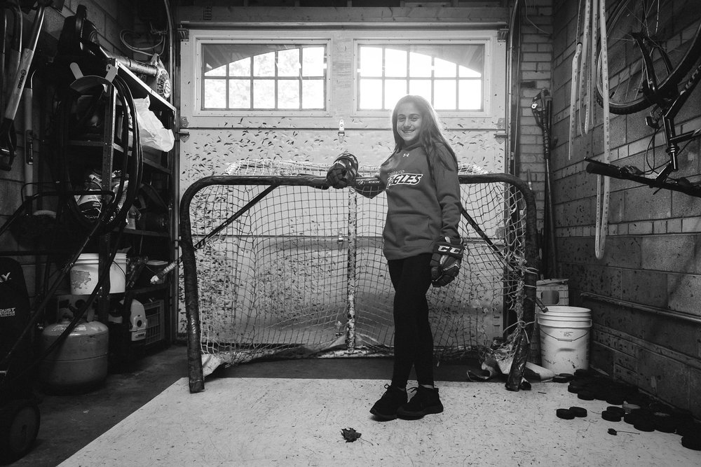 Emma Venusio standing in front of a hockey net in her garage