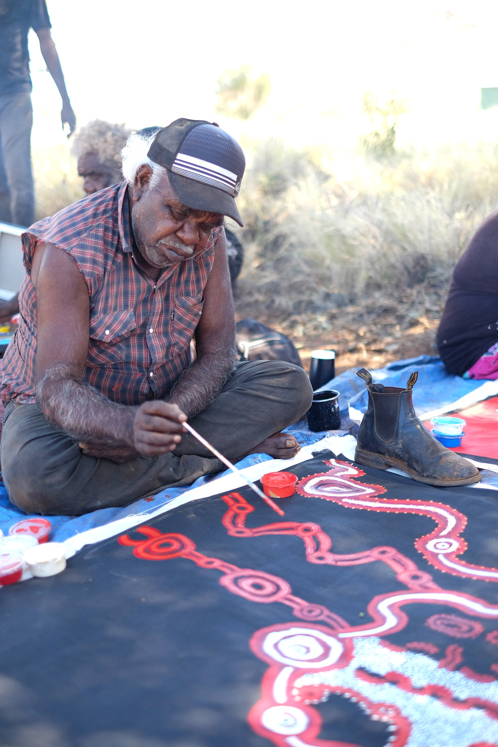 Mr David Miller painting outside of Kalka community, APY Lands, 2018. Photo by Melanie Henderson, Ku Arts.