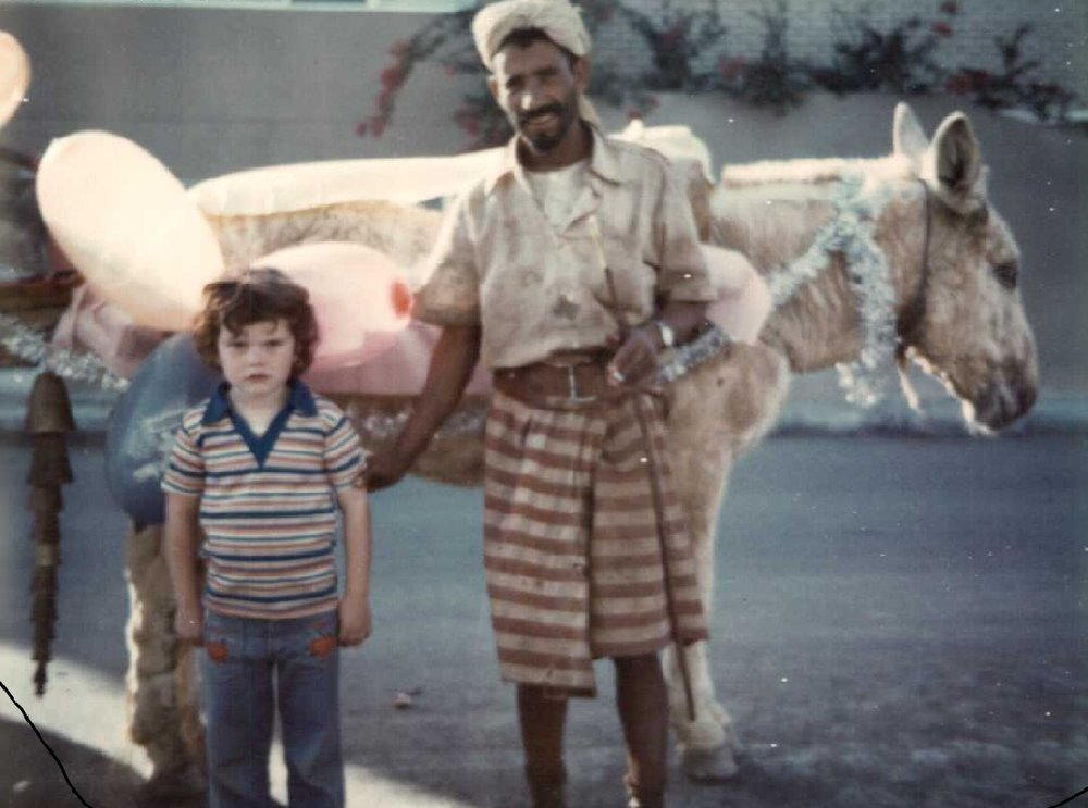 My Son Christopher, looking a bit trepidiacious, posing with a Yemeni donkey cartsman.