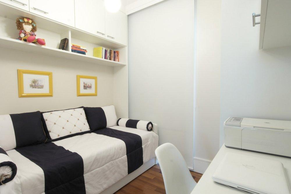 Os armários sobre a cama complementam o espaço para todos os livros. -