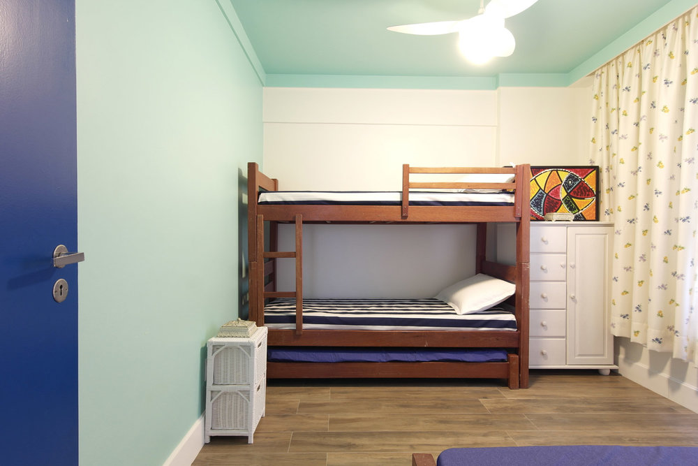Na cortina, florezinhas delicadas e nas colchas, listras azul marinho complementam a cor das portas. -