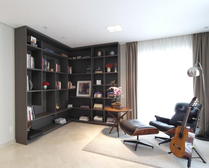 Uma grande estante acomoda os livros, fotos e recordações de família. A Eames Lounge Chair foi eleita para completar o espaço de leitura, junto ao violão, que é um hobby do cliente. -