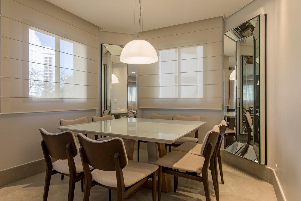 A sala de jantar foi colocada na área menor mais recuada. As paredes chanfradas ganharam espelhos que refletem o restante da sala, dando mais amplitude e integração. -
