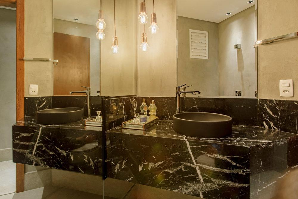 No lavabo, a cuba preta ajuda a destacar o desenho dos veios da bancada em mármore Nero Marquina e mais uma vez aparece o cimento queimado nas paredes e o cobre na luminárias. -