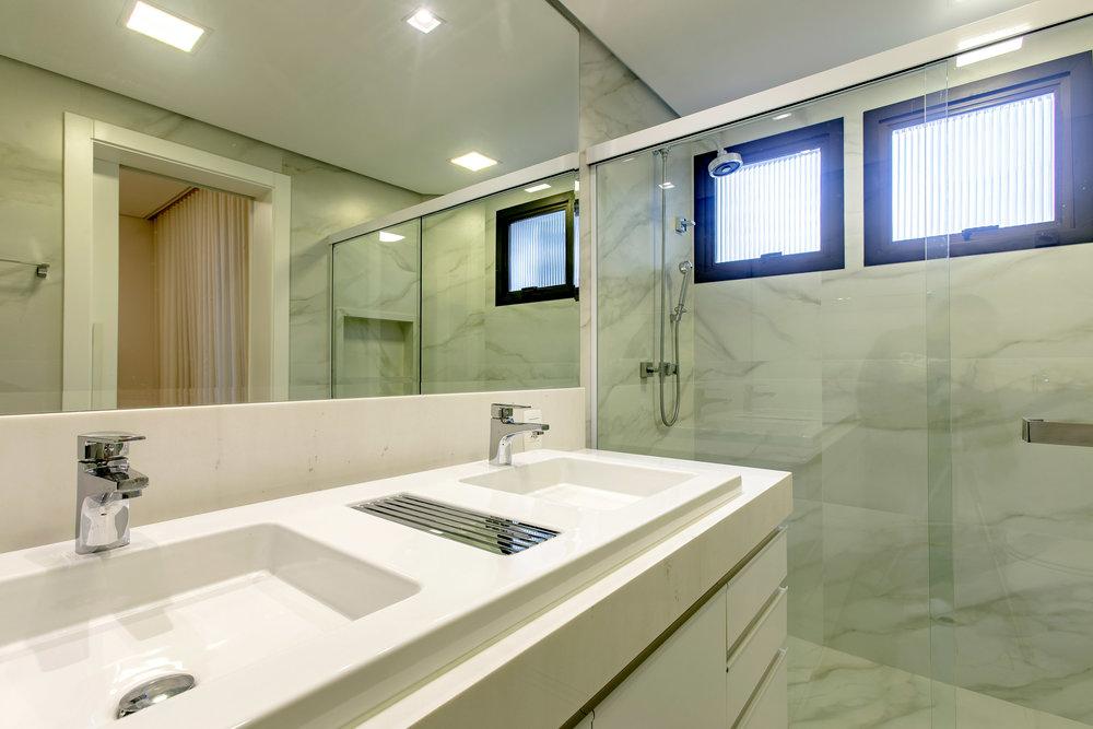 Todos os banheiros possuem a mesma linguagem, com porcelanato claro marmorizado, bancada branca e muito espelho. -