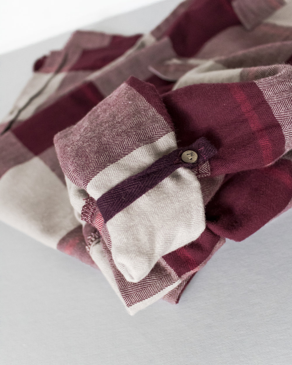 this cozy flannel features coconut buttons up the front and on the sleeves to secure a rolled cuff.