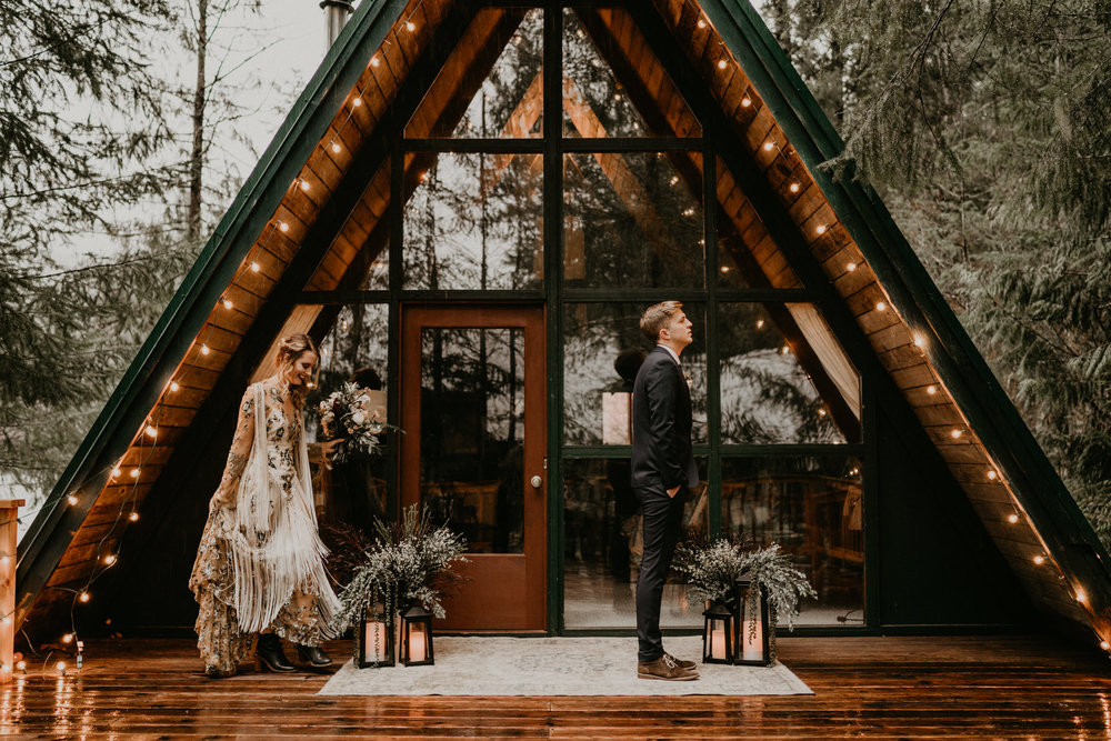 First look between bride and groom from their PNW elopement in front of an A-frame cabin