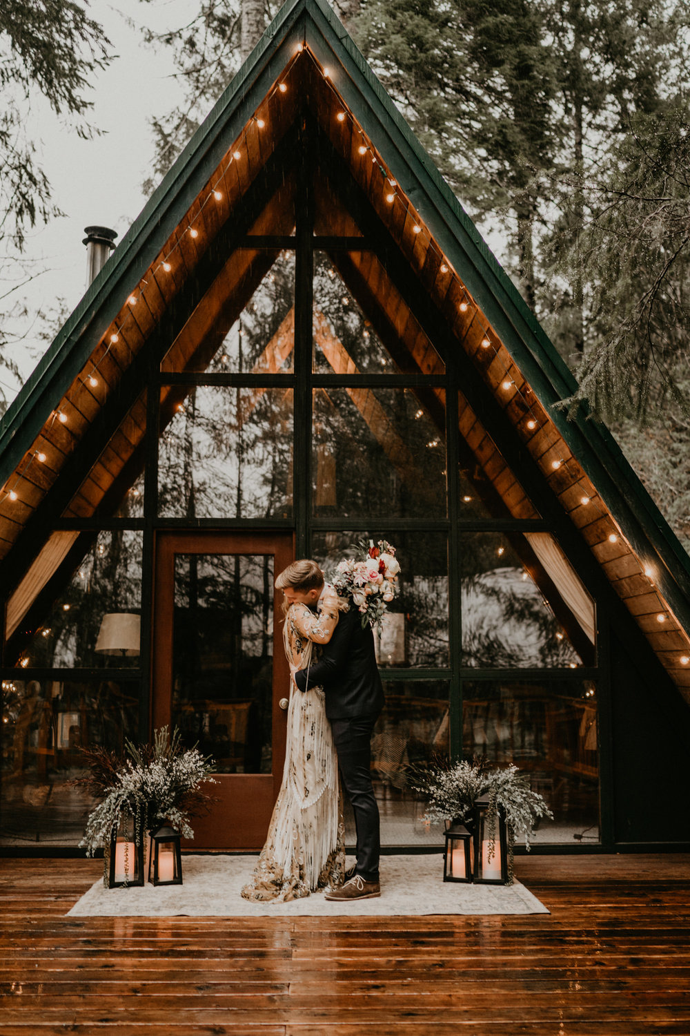 Bride and groom kissing in front of A-frame cabin for their elopement