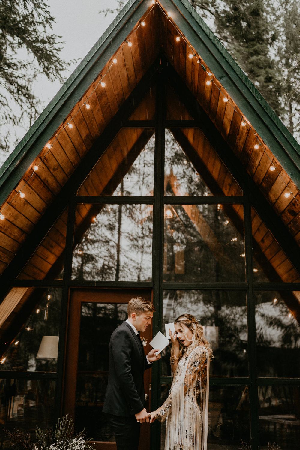 Bride and groom crying from their wedding vows in front of A-frame cabin