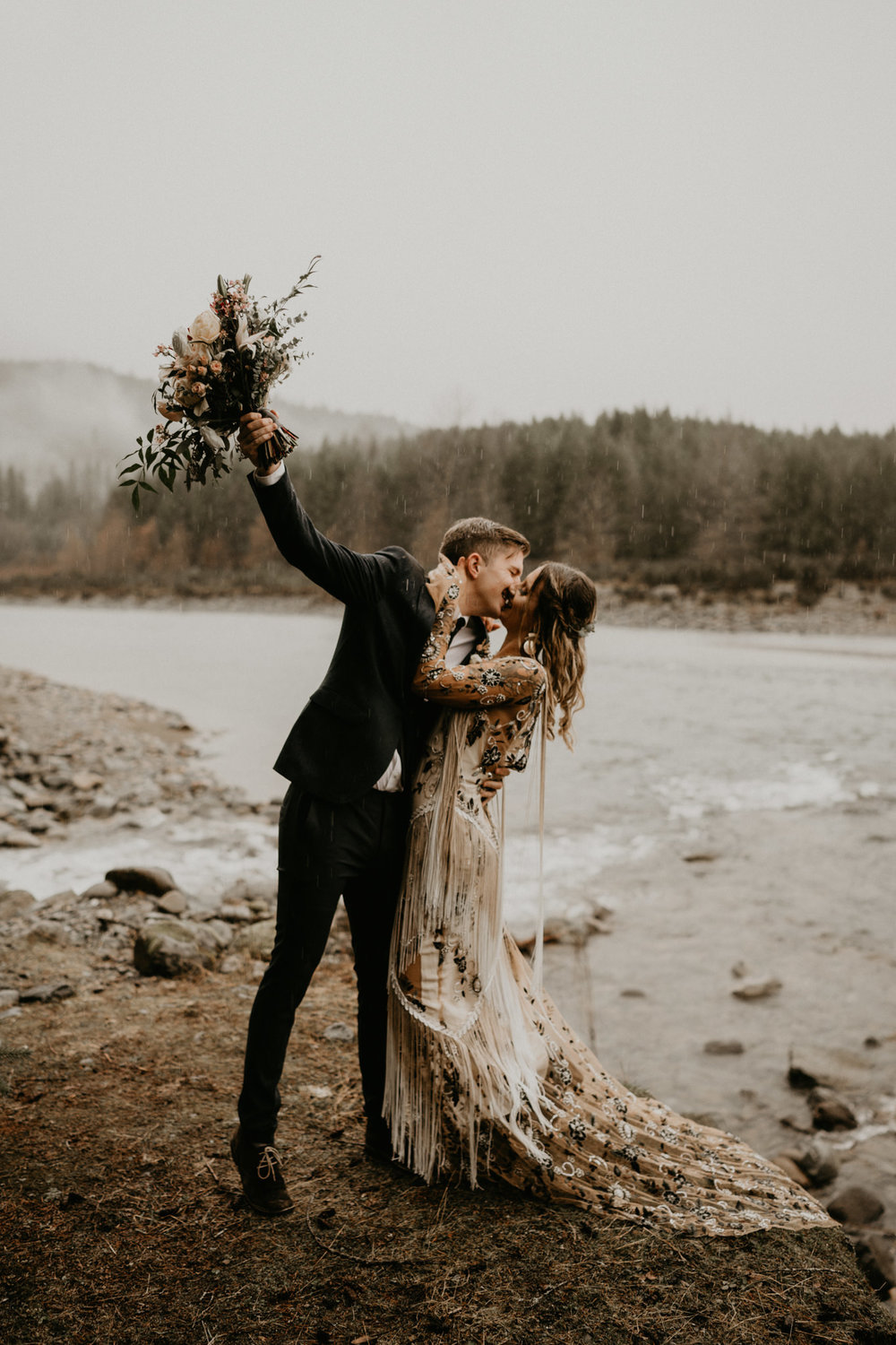 Newly weds kiss in a rainy PNW elopement with rue de seine bridal gown