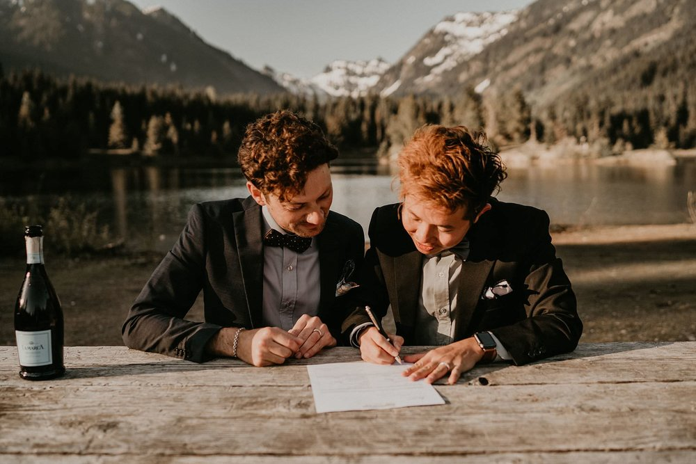 Same sex couple signing marriage certificate in front of beautiful mountain views