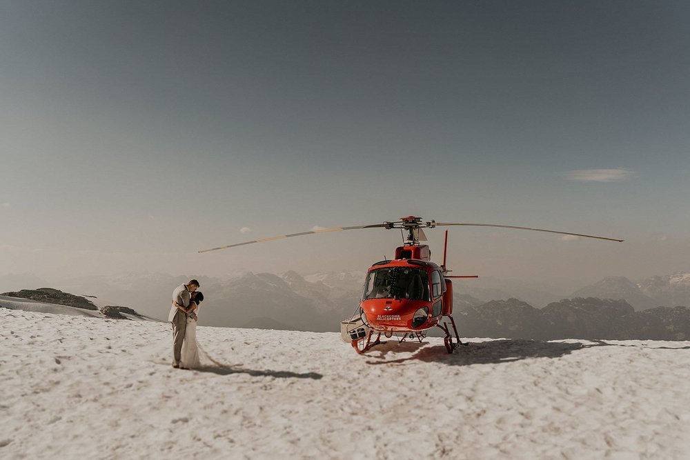Couple kissed in front of blackcomb helicopter on Whistler Mountain after their epic and adventurous elopement