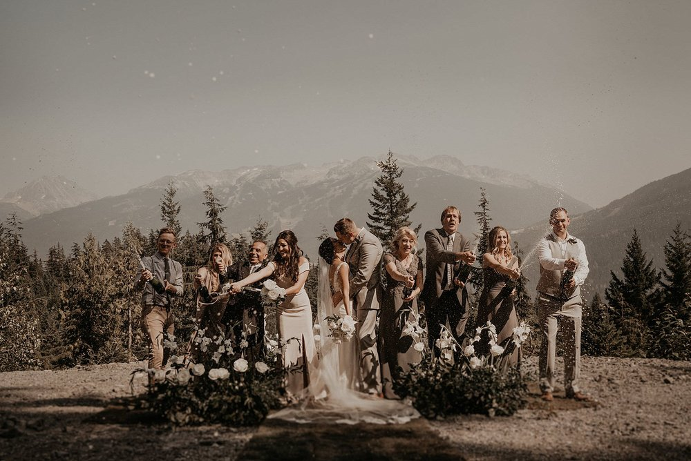 Popping champagne bridal party photo in whistler mountain Canada