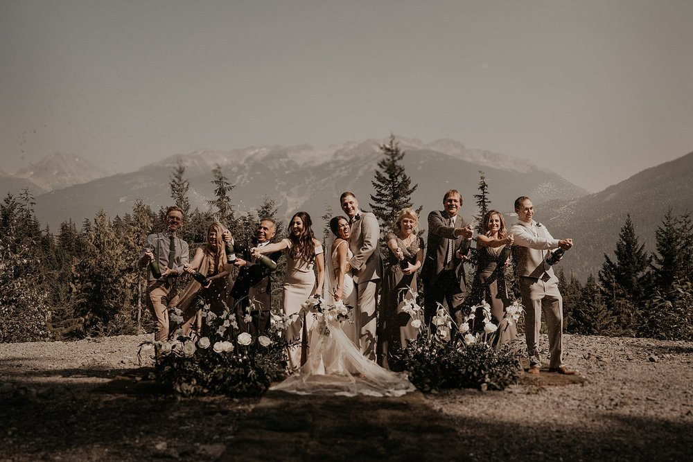 Epic adventure elopement popping champagne with family on mountains