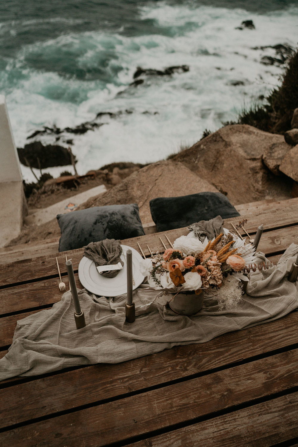 Big Sur Elopement photography of cake and romantic set up by be beach on cliff