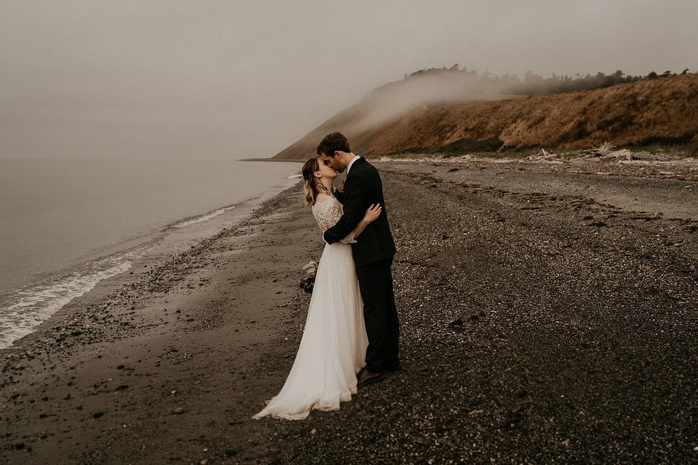 Married bride and groom kissing on the beach in Big Sur California