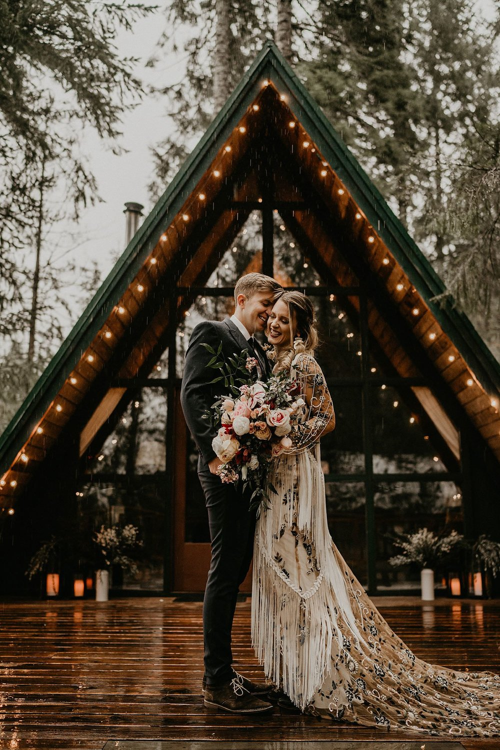 Bride and groom elope in front of an a-frame cabin in the woods of the Pacific Northwest