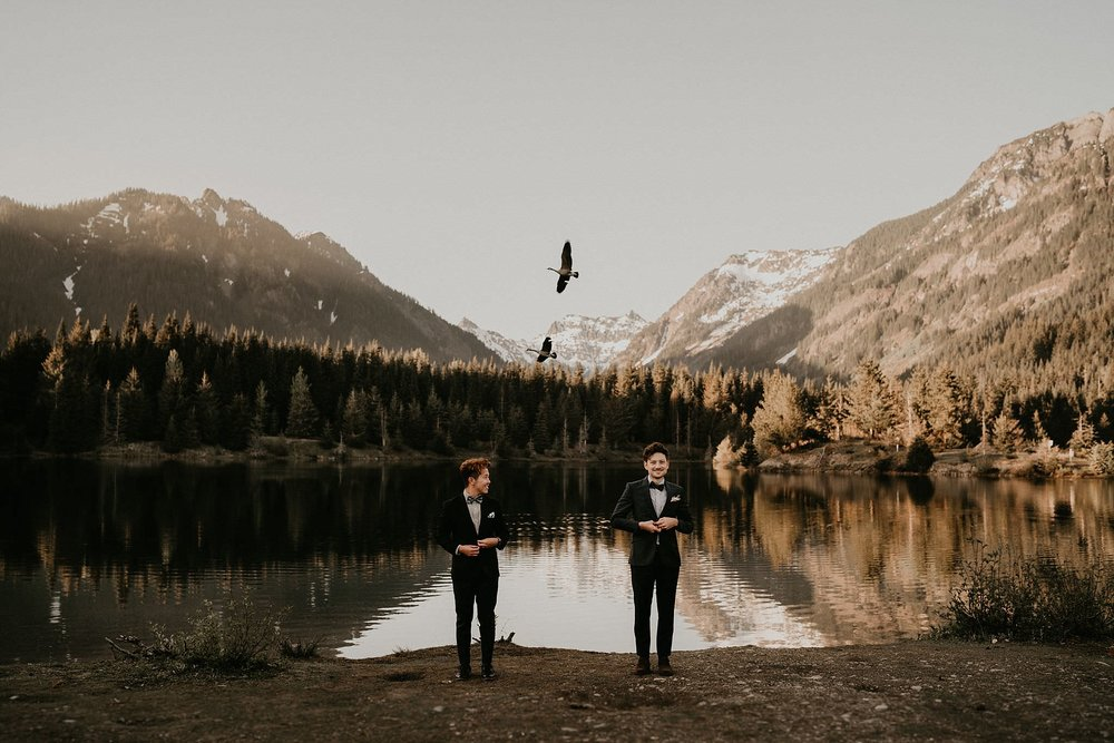 Gay couple married in front of an alpine lake in the mountains outside of Seattle Washington