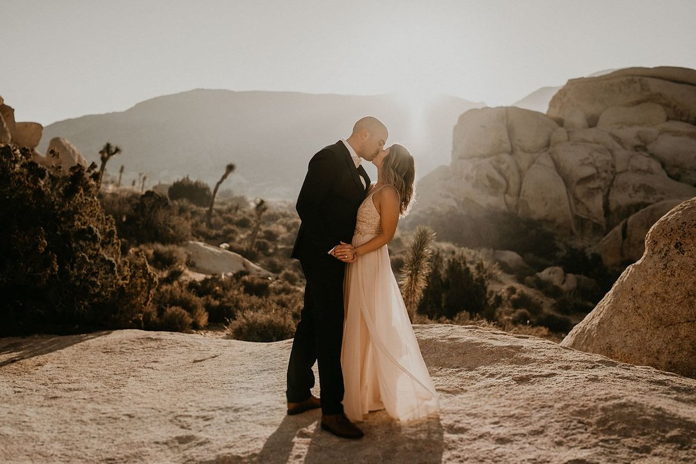 Engagement photo of couple kissing during sunrise in Joshua Tree national park