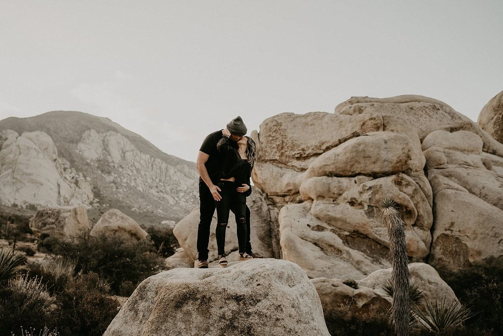 Couple standing on rocks at Joshua Tree National Park for their engagement photos