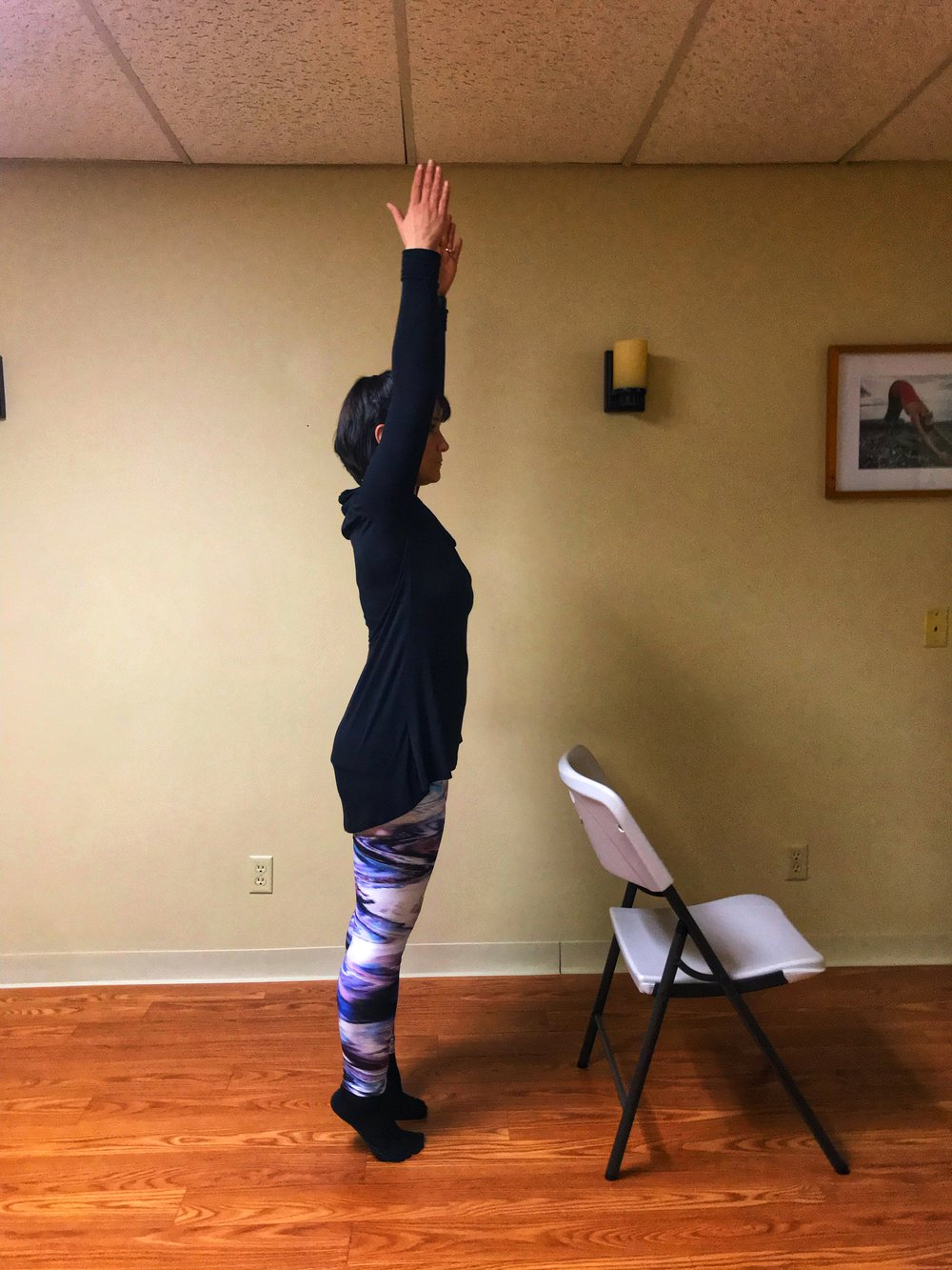 To make this pose harder, extend your arms upright as you lift your heels. To make this pose easier, sit down in a chair and life your heels off the floor, hold, then lower your heels to the floor. Repeat.