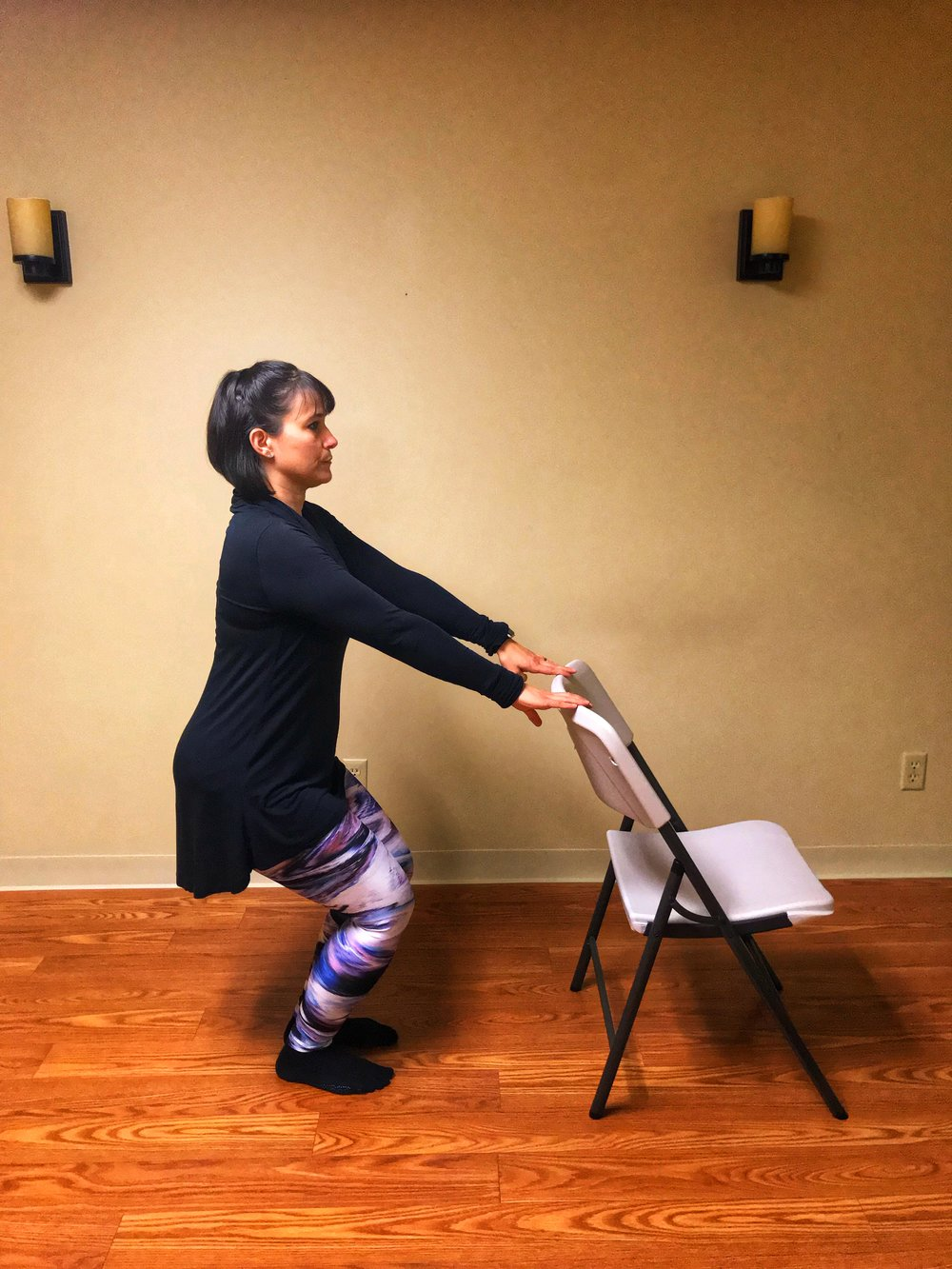 Sit back as if sitting in a chair. Use a chair in front of you to remain stable or if your balance is shaky. Your feet should be flat on the floor, hip width apart, and directly beneath your knees.