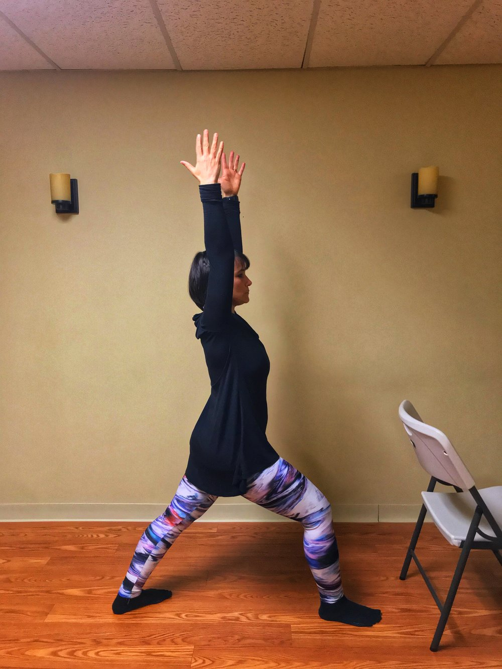 As you become stronger and more flexible, you can try this pose without a chair, raising both arms overhead. Keep the movement slow and controlled and make sure to keep your front knee over your ankle. Tighten your abdominal muscles to support your back.