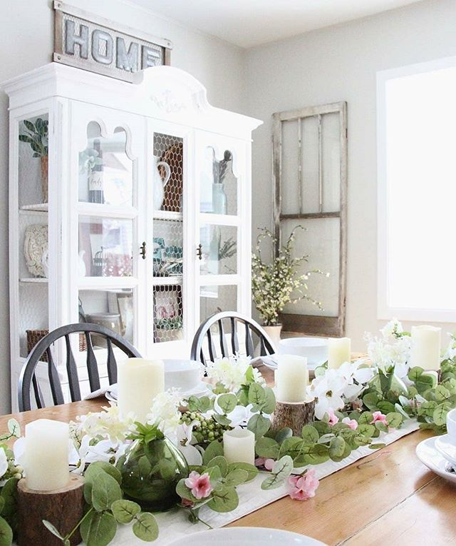 Spring is in the air and nowhere is it more evident than in this dining room from Emily @re.recreate  This tablescape is fun, fresh and floral, filled with natural accents and finished off with a crisp white table runner.  We love the natural log candle pedestals that help ground all of the whites, and the interwoven greenery with flowers peeking out here and there is the perfect touch. This is just the bright sunny spot for lunch with friends, don't you think? . . . . . #farmhousetables #farmhousetablescape #springtablescape #bringonspringtime #farmhousediningroom #farmhousedecorating #farmhousefresh #decoratingwithflowers #decortrends #decorationideas #tablescapes