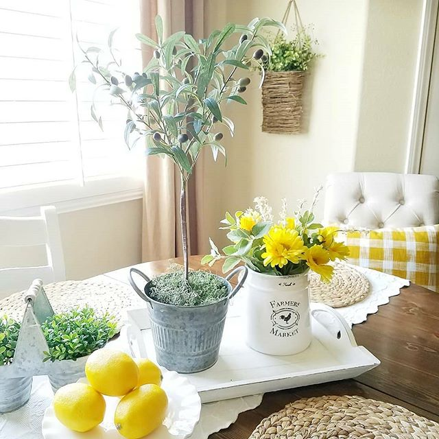 Every day is a sunny day in Sheila's @blessed_at_home  dining room! This bright and cheery room is the perfect place to catch up with your girlfriends or have that morning cup (or seven) of coffee. We adore the white, yellow.and green color combo!! Sheila made her adorable olive tree decor (she has some amazing DIY projects on her blog), and she has styled it perfectly with  fresh flowers, lemons and a darling pair of boxwoods in tiny tins. . . . #olivetree #diywin #sunnyday☀️ #farmhousediningroom #farmhousedecorating #lemondecor #boxwood #farmhouseblog #farmhousechic #farmhousestyledecor