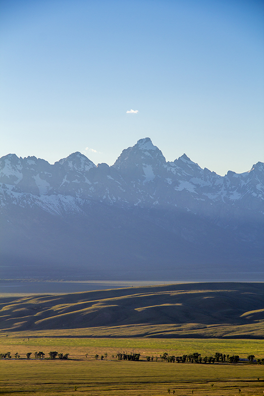 The Grand Tetons during sunset as the sun is behind the mountains.