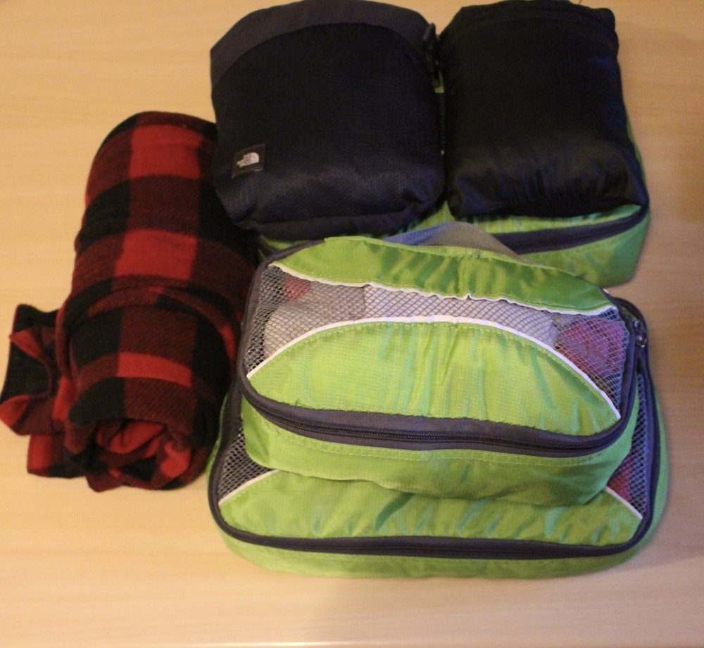 The larger green cubes have my shirts and trousers, the smaller one has my underwear. North Face trousers and my raincoat are at the top, and my flannel on the left.