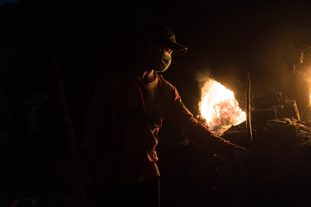 Atith stokes the fire of a kiln at night to minimise the extreme temperatures he faces. Workers experience severe dehydration, heat exhaustion, and even premature death.
