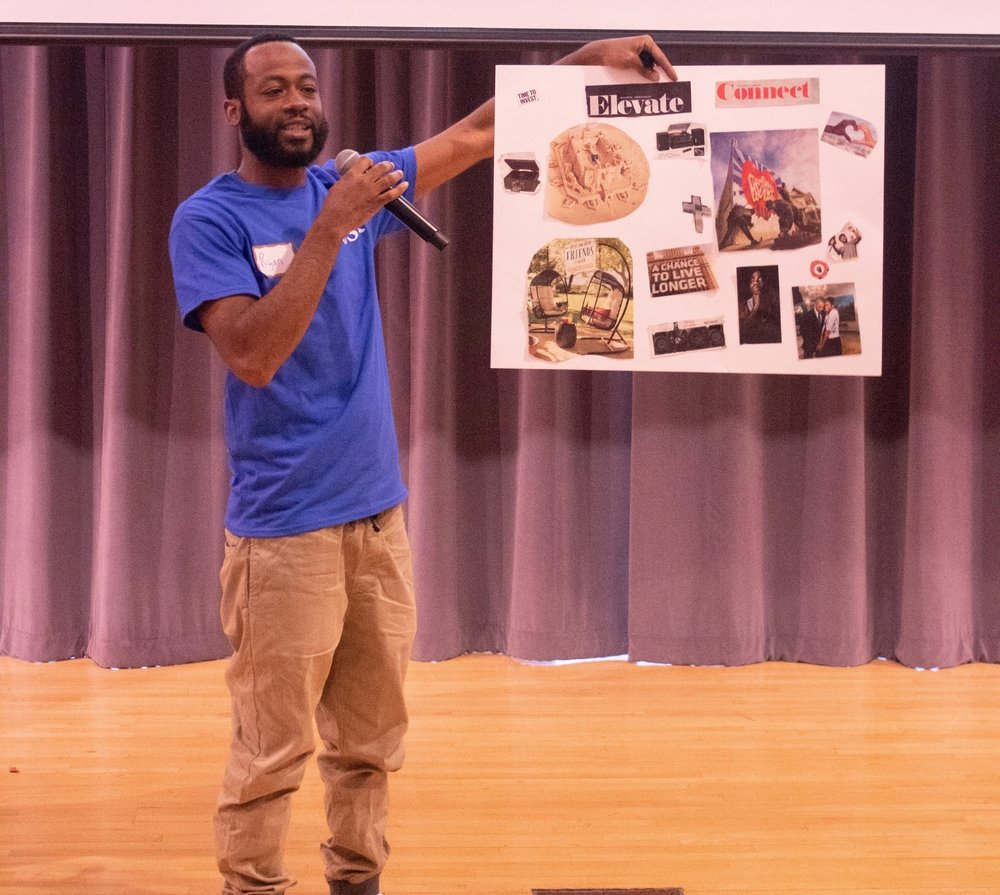 A Children's Services of Roxbury staff member shares his vision board with the room.