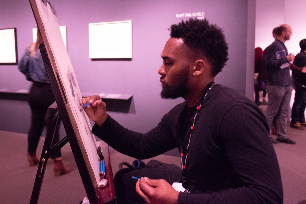 Artist Mykeal Damien Tucker working hard on his drawing.