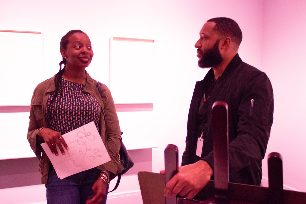 Artist James Pierre chats with a museum guest.