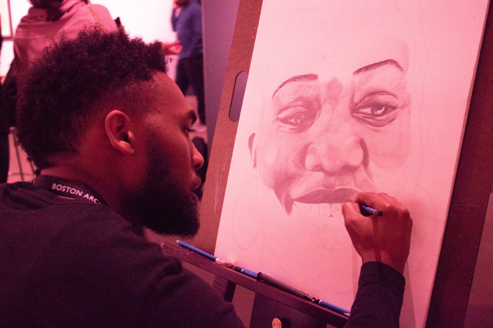 Mykael Damien Tucker works on a portrait of his sister.