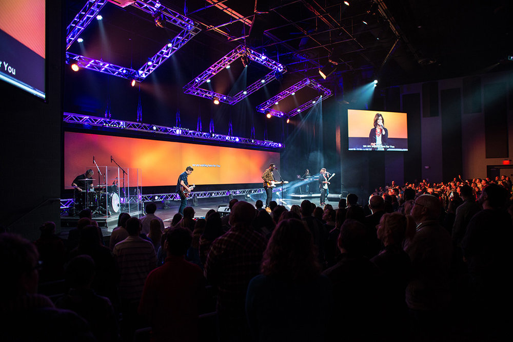 Lifepoint Church began in 2006 with 50 people meeting in a high school auditorium. Today they have two services with an average weekend attendance of over 1,200 persons. They purchased an ice rink building in a popular commercial development in Fredericksburg, Virginia and renovated it into a 1,000 seat seat stadium-style worship space with a 2,000 square foot stage and state-of-art video and lighting. Children's ministry spaces have their own band-ready worship venues, classrooms are flexible, offices are modern, and the flow is welcoming.