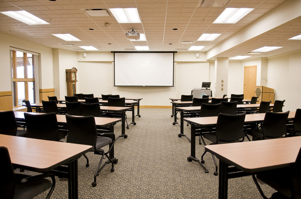 We were tasked with converting an underutilized lecture hall to a conference center and offices. By leveling the existing sloped floor we increased the space's flexibility. We created a main conference room that would accommodate lectures for 75 persons and conferences for up to 40 persons. Finishes, trim and furnishings were carefully selected for acoustic performance, durability and creation of an executive image. A suite of offices was added for the Human Resources department and through reducing the ceiling height we were able to add a much-needed classroom to the floor above.