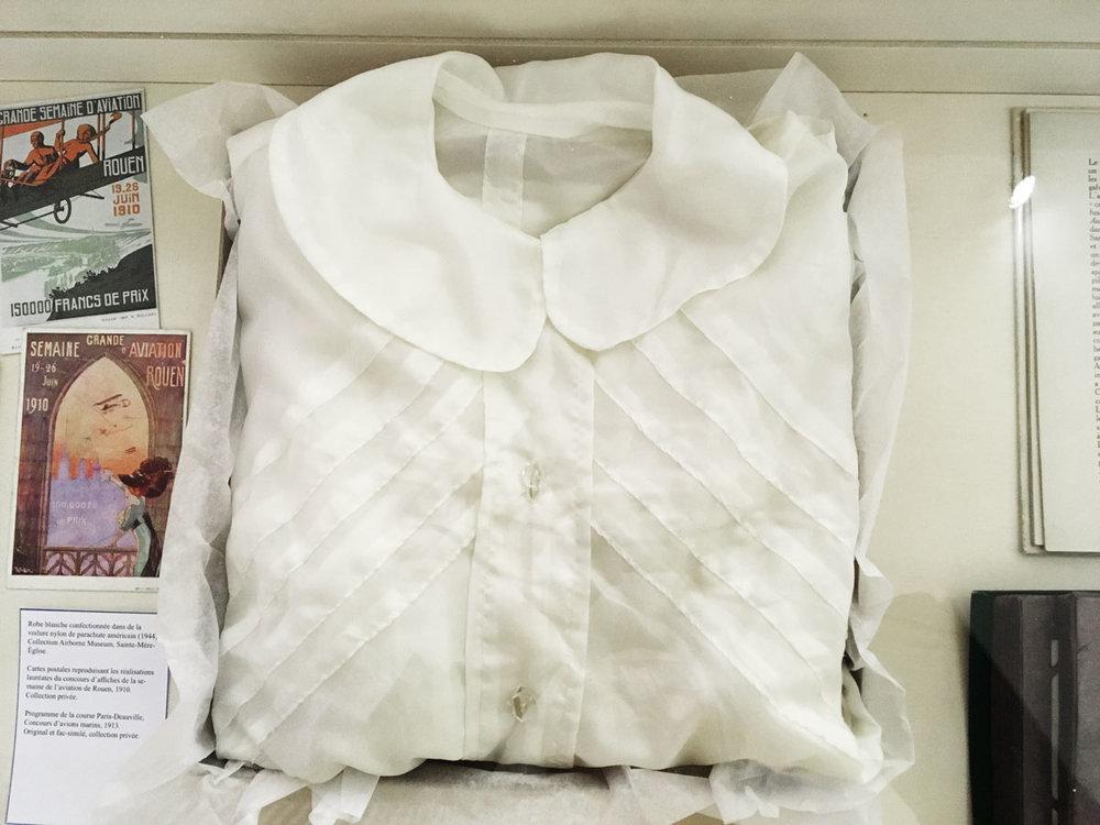 Robe blanche confectionnée dans la voilure de nylon d'un parachute américain. 1944 - Egalement présentés dans l'exposition, des objets évoquant les débuts de l'aviation.